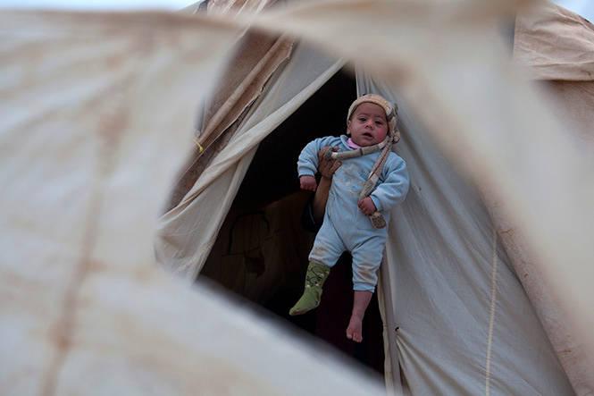 Seorang ibu menyembunyikan jati dirinya sambil mengangkat bayinya di sebuah tenda keluarga di Zaatari, kamp pengungsi warga Suriah di Yordania, 5 Februari. Pada Januari, International Rescue Committee menyebut kekerasan seksual sebagai alasan utama para wanita dan gadis melarikan diri dari Suriah. (Heidi Levine/Sipa Press)