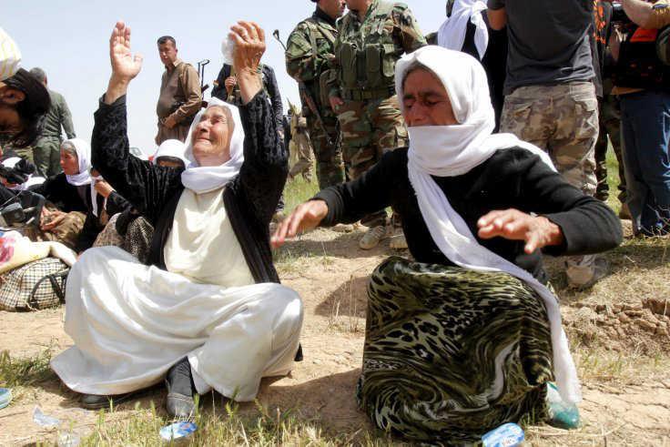 Para anggota minoritas Yazidi yang baru dibebaskan sedang menunggu di sebuah jalan di pinggiran Kirkuk. (Reuters)