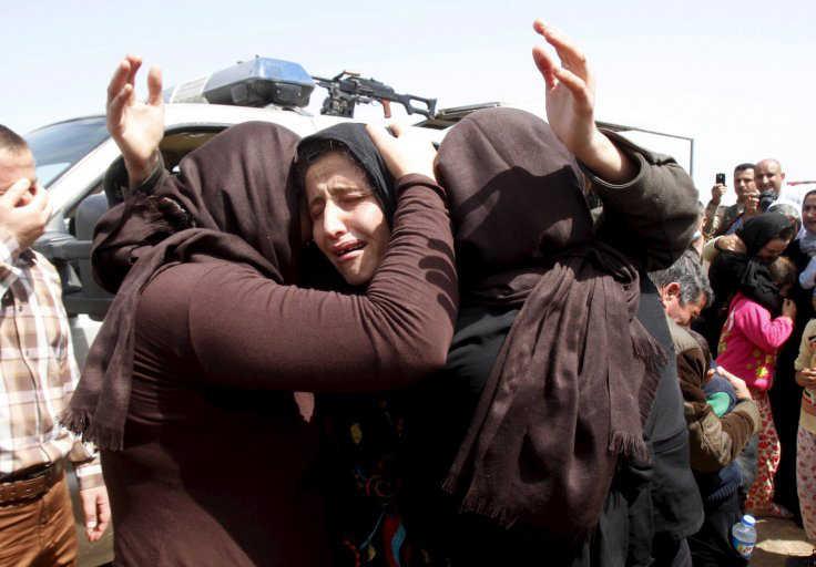 Para anggota sekte minoritas Yazidi yang baru dibebaskan saling berpelukan di pinggiran Kirkuk. (Reuters)