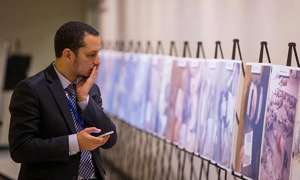 Seorang pria bereaksi saat memandang beberapa foto Caesar, di PBB, New York. Foto: Lucas Jackson/Reuters
