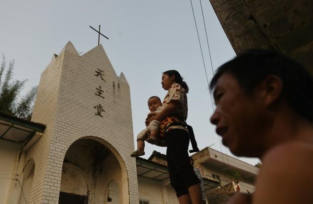 Penduduk desa berdiri luar gereja Katolik di Changjing, Guangxi, wilayah selatan China. ©Greg Baker (AFP)