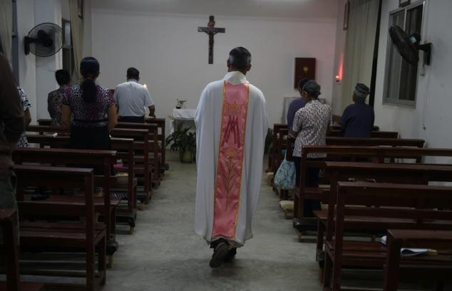 Seorang pastor memulai Misa di gereja Katolik di Dingan, Guangxi, wilayah selatan China. ©Greg Baker (AFP)
