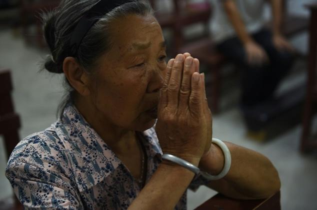 Seorang anggota paroki pada saat Misa di gereja Katolik di Dingan, Guangxi, wilayah selatan China. ©Greg Baker (AFP)